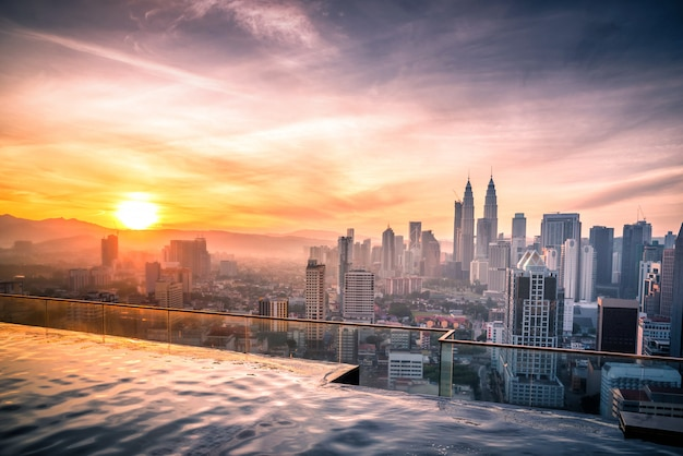 Arquitetura da cidade da skyline da cidade de kuala lumpur com piscina na parte superior do telhado do hotel no nascer do sol em malásia.