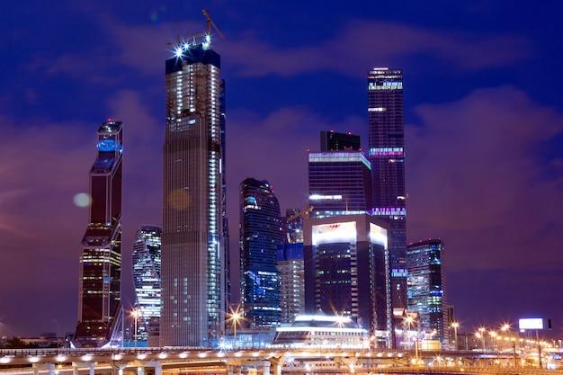 Arquitetura de negócios - arranha-céus e trilhas leves. centro de negócios moderno nas luzes da noite