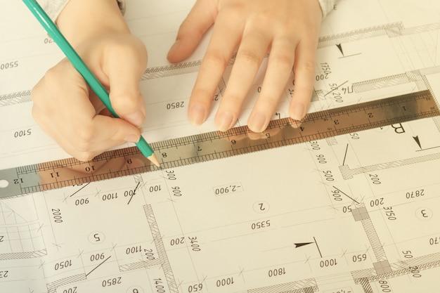Arquitetura e construção. um arquiteto desenha um plano em um estúdio arquitetônico em uma mesa