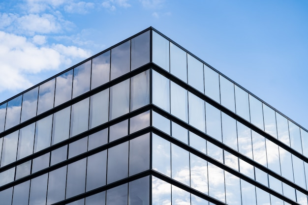 Arquitetura moderna de edifício de vidro com céu azul e nuvens
