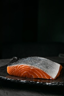 Arquivo de salmão cru no quadro cinza e superfície preta