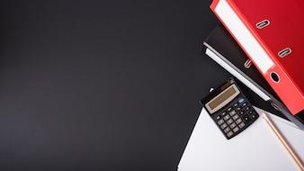 Arquivo vermelho; calculadora; lápis e white papers sobre fundo preto