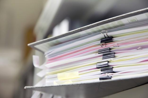 Arquivos de documentos empilhados com clipe de papel preto nas prateleiras.