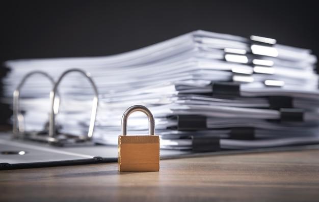 Arquivos e documentos com cadeado na mesa de madeira. segurança de dados
