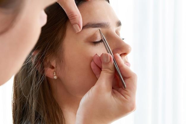 Arrancar sobrancelhas femininas com uma pinça durante a correção de sobrancelhas no salão de beleza