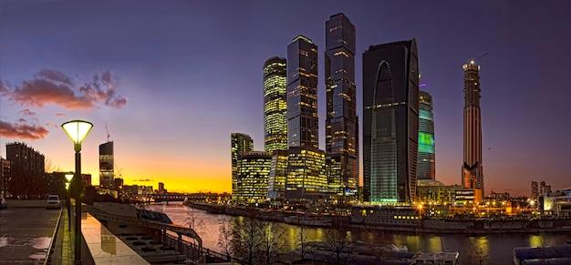 Arranha-céus da cidade de moscou nas margens do rio moscou à luz das luzes da noite