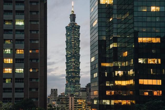 Arranha-céus de taipei 101 no crepúsculo com edifícios comerciais no primeiro plano.