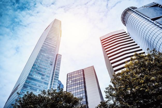 Arranha-céus modernos comuns do negócio, prédios, arquitetura que levanta para o céu, sol. conce