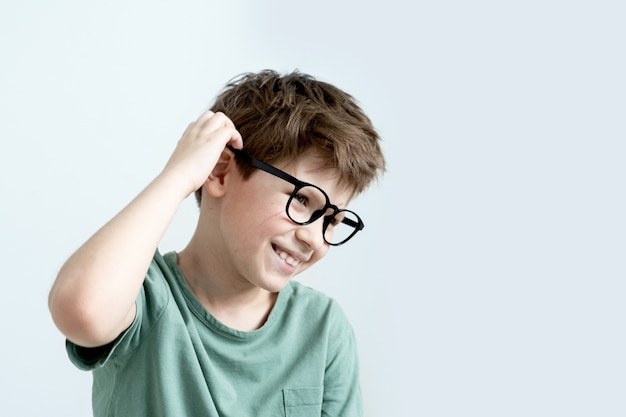 Arranha-se, menino surpreso com uma camiseta verde e óculos pensativo coça a cabeça