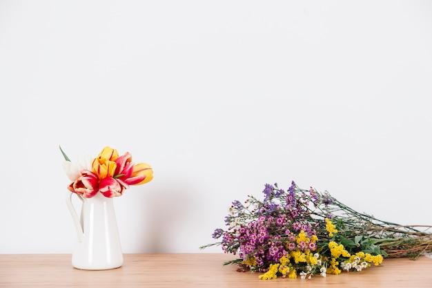Arranjaram tulipas e flores silvestres na mesa