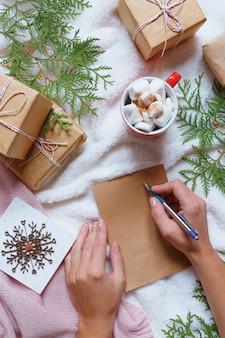 Arranjo aconchegante festivo de natal, as mãos da mulher escrever uma carta para o papai noel, caixas festivas,