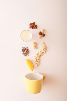 Arranjo alimentar, aveia, fatia de laranja, cacau, leite, avelãs, castanha de caju, amêndoas e passas caindo em uma tigela amarela sobre um fundo claro. conceito saudável do pequeno-almoço alimentar.