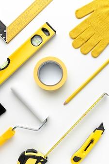 Arranjo amarelo de luvas e ferramentas de construção