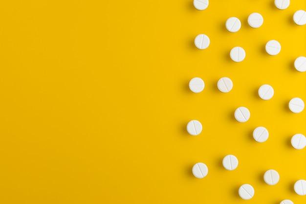 Arranjo branco dos comprimidos da medicamentação no fundo amarelo. lay plana. copie o espaço.