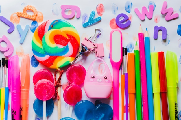 Arranjo brilhante de canetas escolares e pirulitos