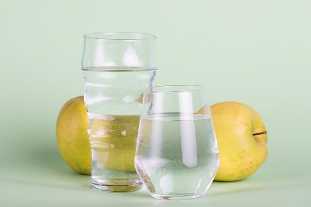 Arranjo com água e maçãs amarelas