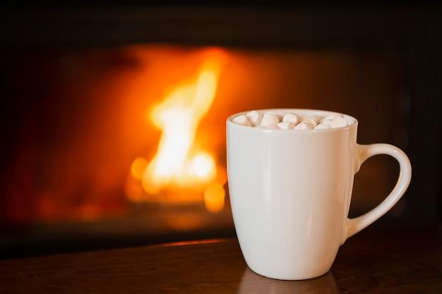 Arranjo com bebida de marshmallow perto da lareira