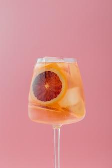 Arranjo com bebida frutada e fundo rosa