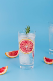 Arranjo com bebidas e fatias de laranja vermelhas