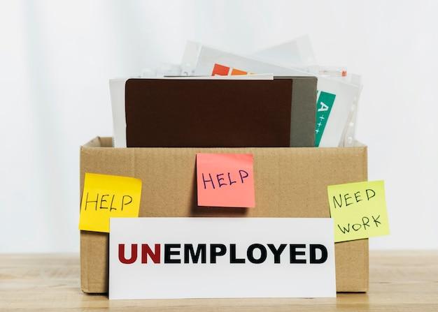 Arranjo com caixa e placa de desempregado