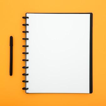 Arranjo com caneta e ntoebook vazio