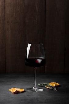 Arranjo com copo de vinho e fatias de laranja