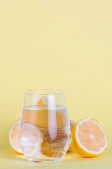 Arranjo com copo pequeno de água e limão