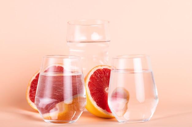 Arranjo com copos de água e laranjas vermelhas