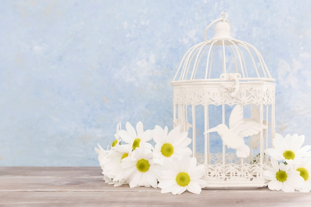 Arranjo com flores e uma gaiola de pássaro