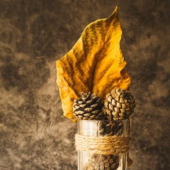 Arranjo com folhas amarelas secas e cones