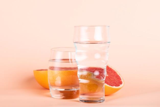 Arranjo com laranja vermelha e copos de água