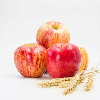 Arranjo com maçãs vermelhas e espigas de trigo