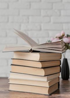 Arranjo com pilha de livros dentro de casa