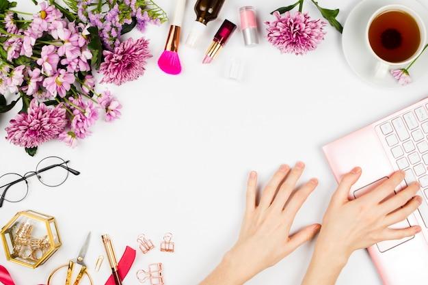 Arranjo com uma xícara de chá, flores, cosméticos, óculos e mãos de mulher, digitando no laptop rosa