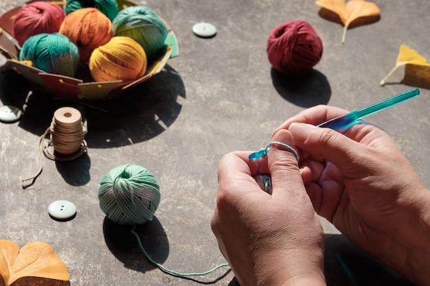 Arranjo criativo de materiais artesanais para tricô e crochê na mesa escura.