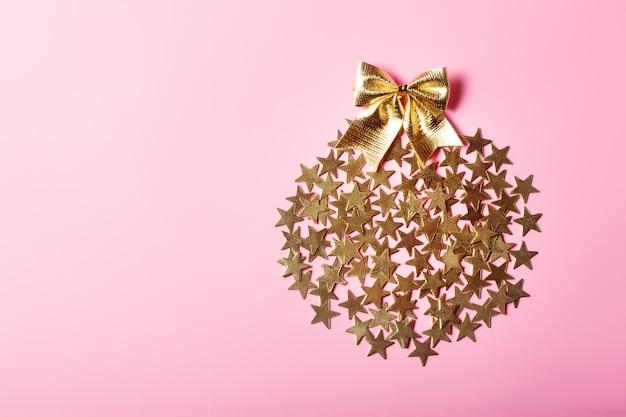 Arranjo criativo de natal com estrelas douradas em círculo sobre fundo rosa, conceito de glamour