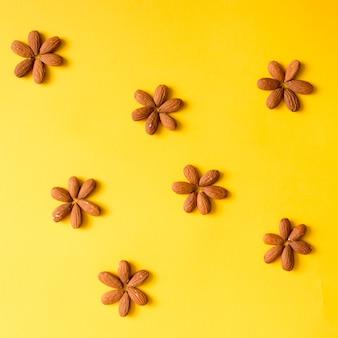 Arranjo criativo de nozes na parede amarela. postura plana.