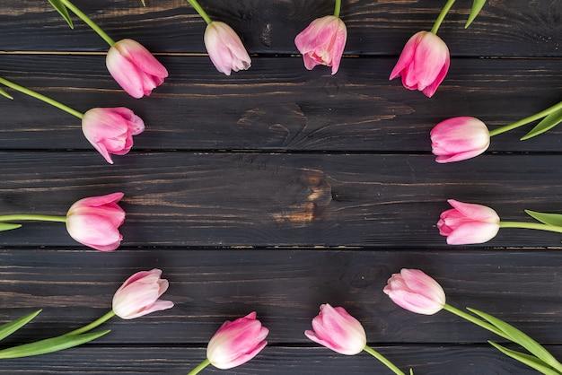Arranjo criativo de tulipas no fundo escuro de madeira. lay plana
