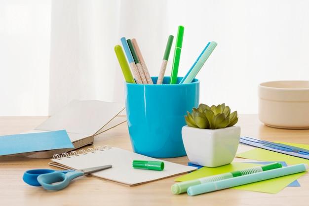 Arranjo da mesa com recipiente para canetas e planta