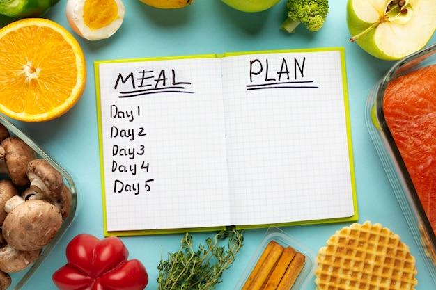 Arranjo da vista superior com caderno de planejamento de refeição