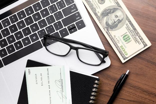 Arranjo da vista superior com dinheiro e cheque