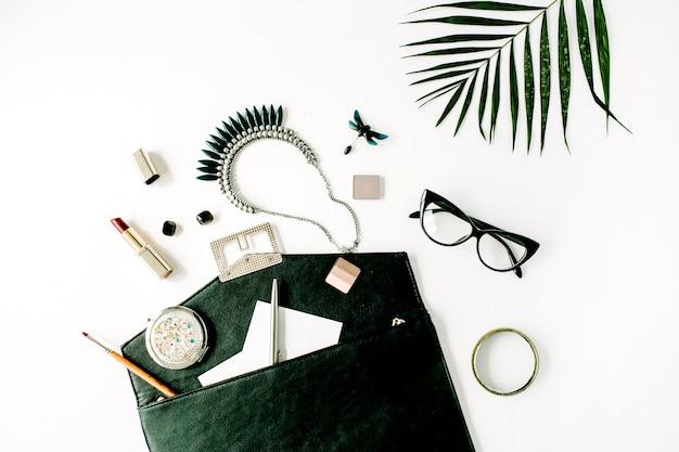 Arranjo de acessórios femininos de beleza com ramo de palmeira, bolsa, óculos, batom e colar