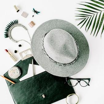 Arranjo de acessórios femininos de beleza com ramo de palmeira, chapéu, bolsa, óculos, batom e colar