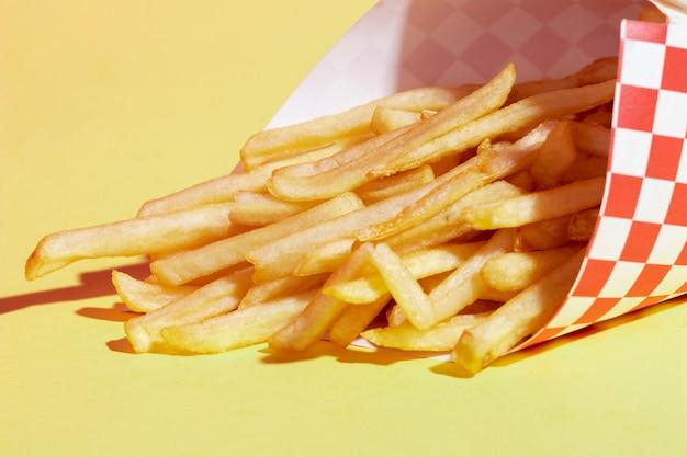 Arranjo de alto ângulo com batatas fritas e fundo amarelo