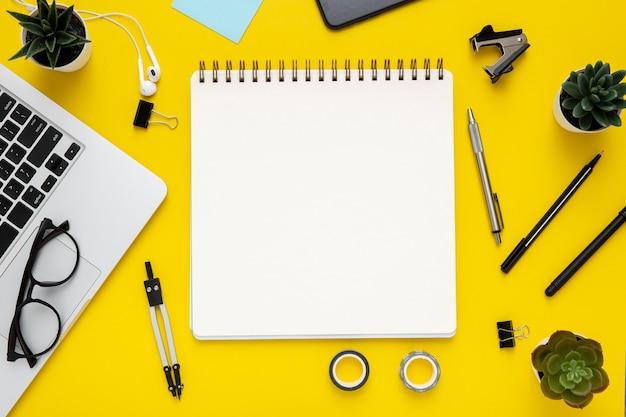 Arranjo de artigos de papelaria em fundo amarelo com caderno vazio