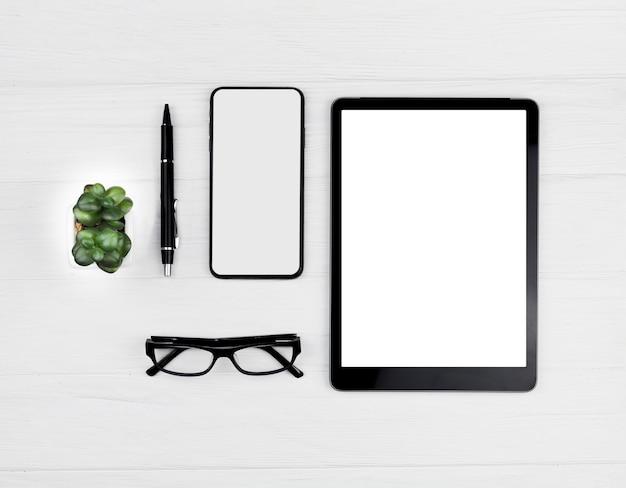 Arranjo de artigos de papelaria vista superior sobre fundo azul com tablet e telefone maquete