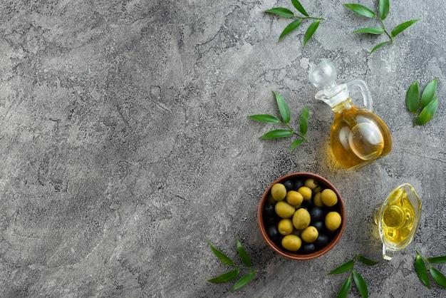 Arranjo de azeitonas e óleos em fundo de mármore