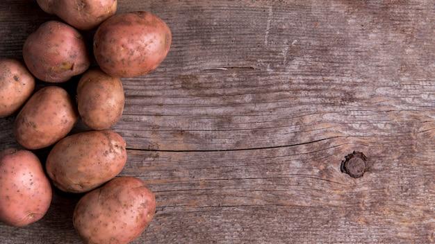 Arranjo de batatas em fundo de madeira com espaço de cópia