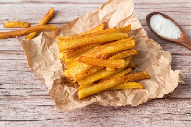 Arranjo de batatas fritas no fundo de madeira