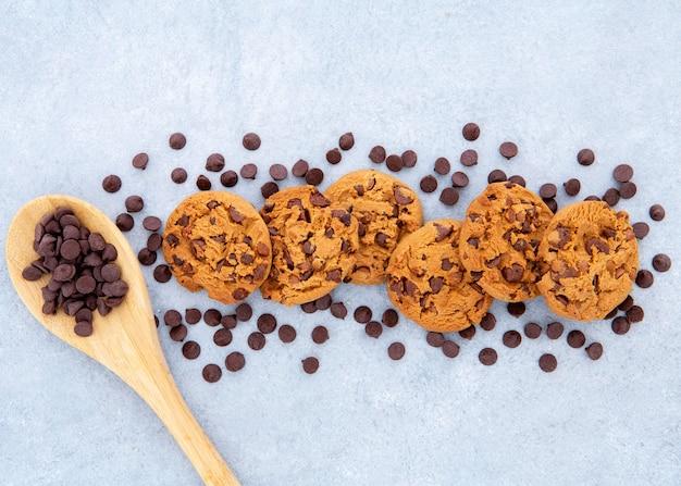 Arranjo de biscoitos rodeado por gotas de chocolate e colher